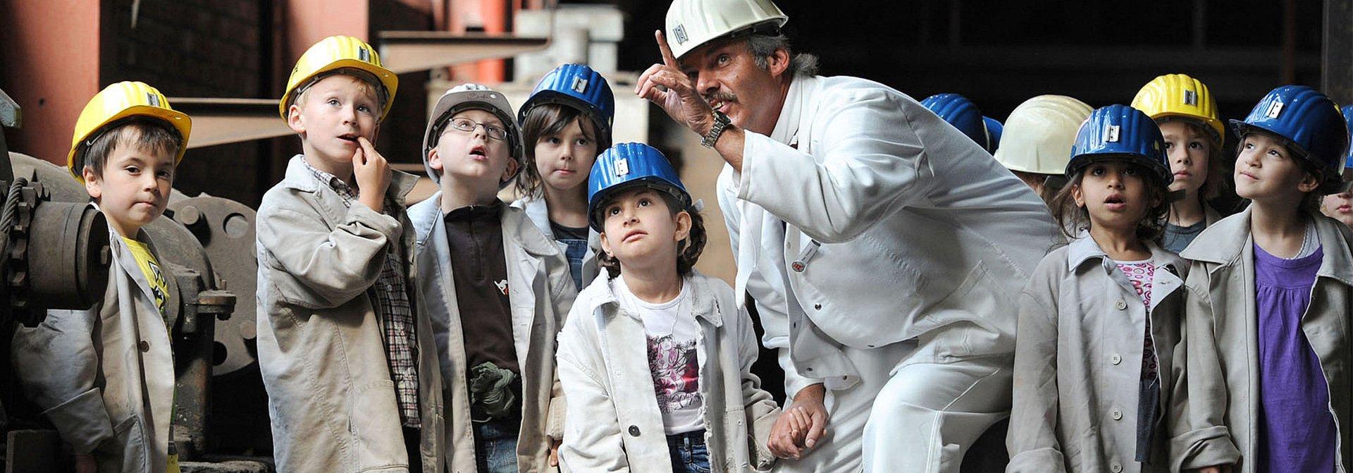 Kinder mit Bauhelm und Schürze hören einem Arbeiter zu