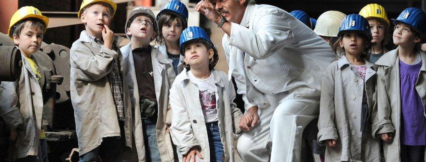 Arbeiter zeigt Kindern eine technische Anlage