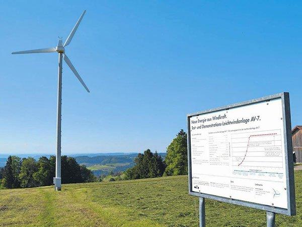 Windrad auf Hügel mit Informationstafel