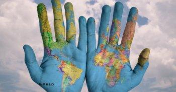 Hände mit dem Muster der Weltkarte