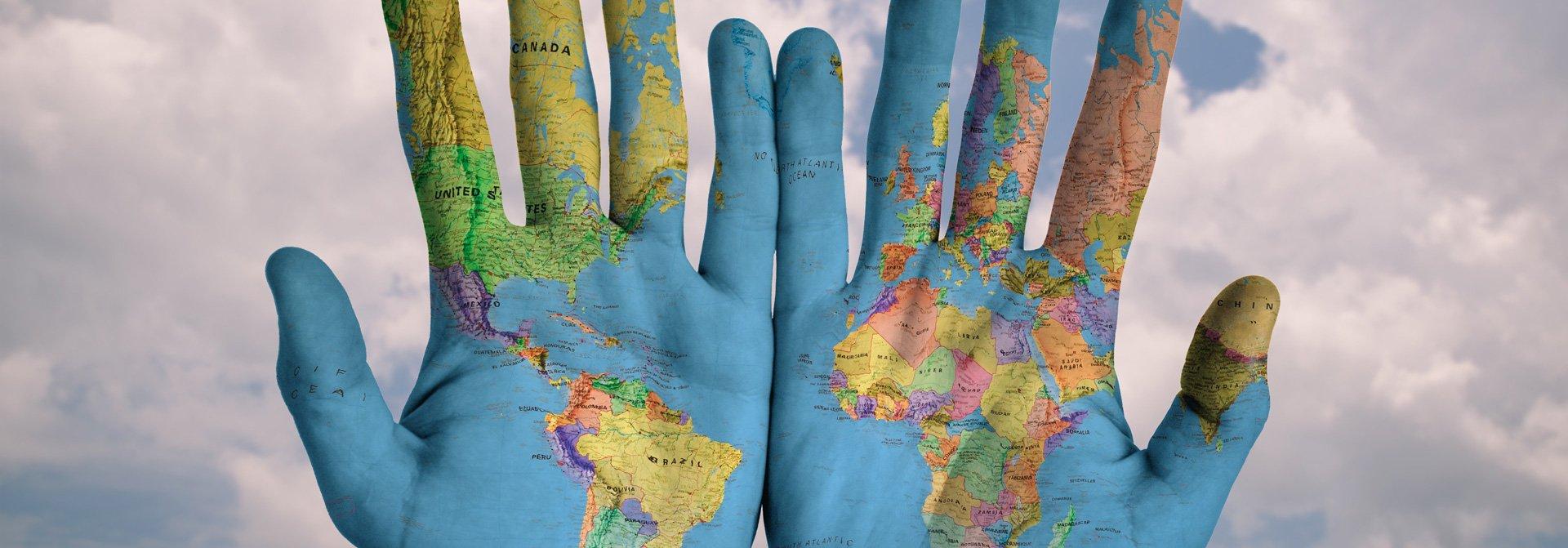 Hände im Muster der Weltkarte