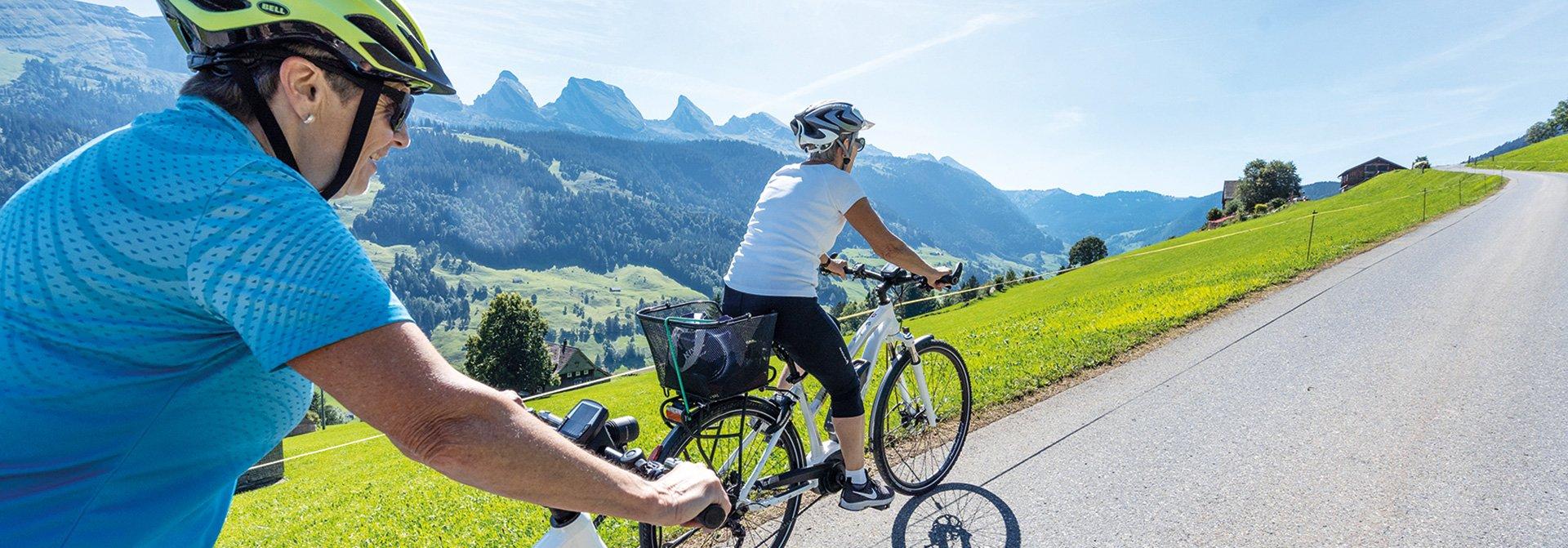 Zwei Frauen fahren auf einer Landstrasse Fahrrad