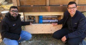 Zwei Arbeiter zeigen die Grauwasseraufbereitungsanlage am Eventhaus