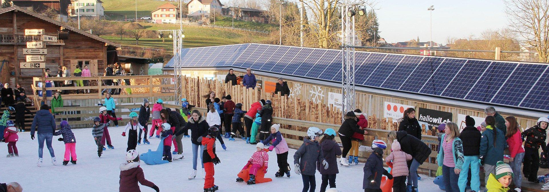 Viele Besucher auf Eisfeld im Freien mit PV-Anlage