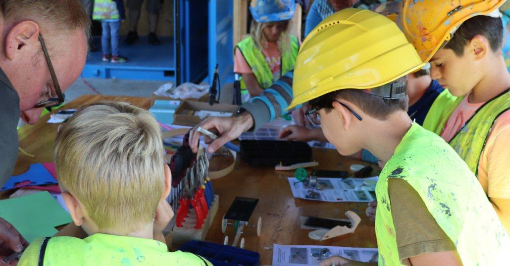 Kinder mit Bauhelm werken auf einer Kinderbaustelle