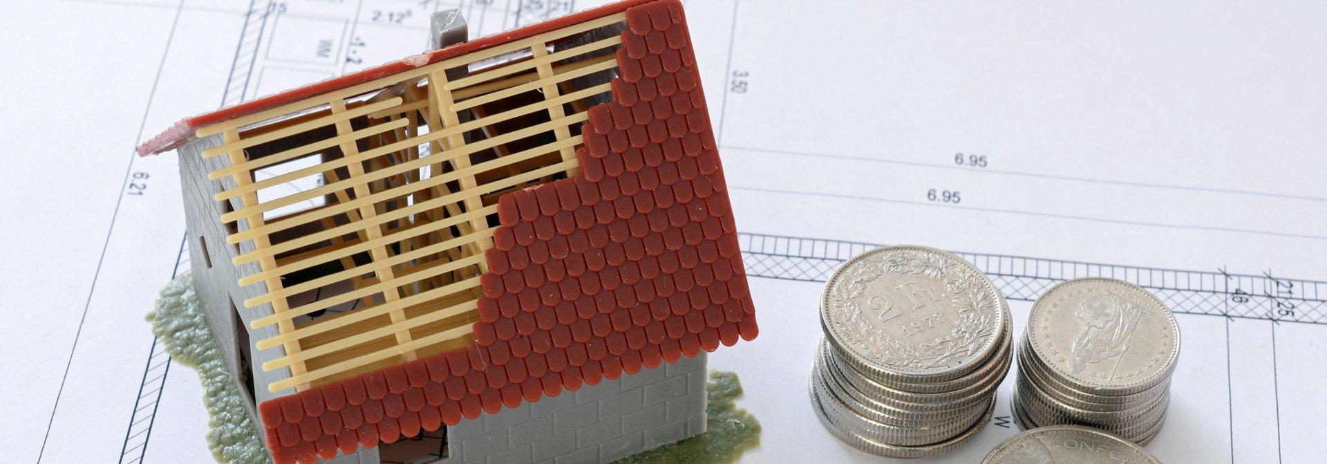Modellhaus auf Bauplan mit Bargeld