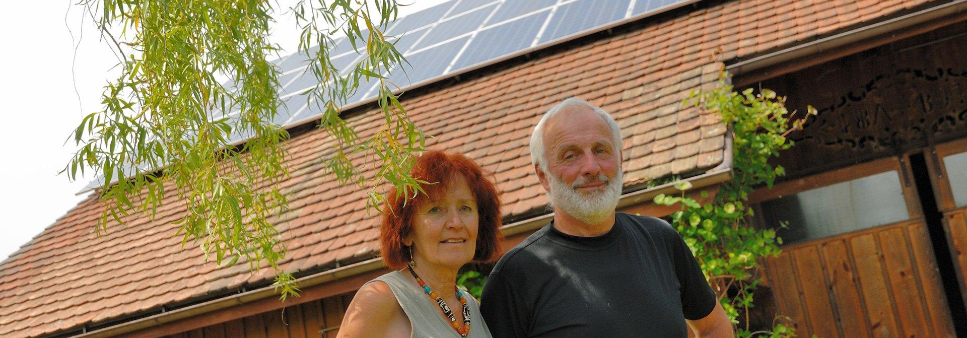 Ehepaar steht vor Scheune mit PV-Anlage