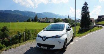 Elektroauto auf Parkplatz mit Dorf im Hintergrund