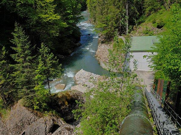 Druckleitung von Wasserkraftwerk neben Fluss im Wald